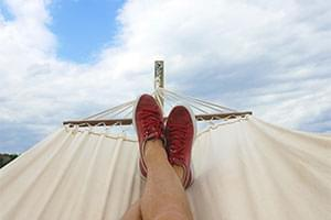 person in hammock with blue sky backdrop